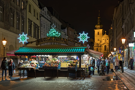 PRAGUE, CZECH REPUBLIC - DECEMBER 5, 2017: Havelsky Market with Christmas decoration in night. Its origin dates back to 1232. Church of St. Gallus (Kostel sv. Havla) is visible in the background.