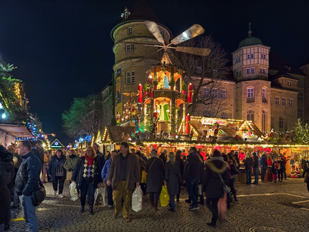 STUTTGART, GERMANY - DECEMBER 14, 2017: Christmas market with Christmas pyramid close to Altes Schloss (Old Castle) in night. The Christmas pyramid is a kind of carousel demonstrating nativity scenes.