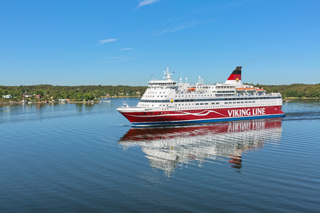 STOCKHOLM ARCHIPELAGO, SWEDEN - JUNE 1, 2018: Cruiseferry MS Gabriella of Viking Line goes along Rindo island. The ship was built in 1992, rebuilt in 2008, and operates on the Helsinki-Stockholm route Standard-Bild - 115577397