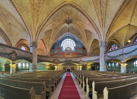 TAMPERE, FINLAND - MARCH 5, 2019: Panoramic view of interior of Tampere Cathedral with main organ. Cathedral was built in 1902-1907 by design of Lars Sonck. Organ facade was designed by Lars Sonck too