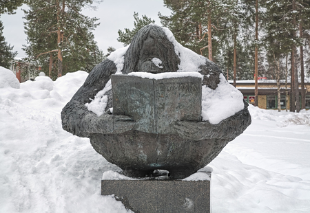 OULU, FINLAND - MARCH 27, 2010: Tiedonjano (Thirst for Knowledge) sculpture depicting an ape which reads book about animals. Sculpture by Raimo Metsanheimo was erected in 1987 in Kaijonharju district.