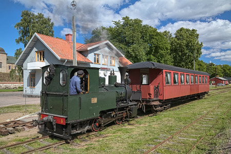 VADSTENA, SWEDEN - AUGUST 25, 2013: Old steam train at Vadstena station of narrow-gauge railway Vadstena-Fagelsta. The railway was put into operation in 1874. Since 1974, it uses as a museum railway.
