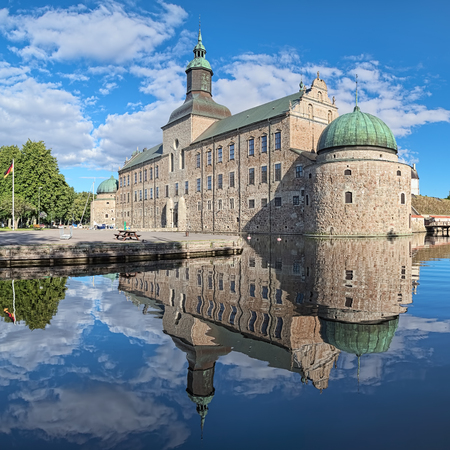 VADSTENA, SWEDEN - AUGUST 25, 2013: Vadstena Castle. The main castle building reflects in the water of moat. Construction of the castle was started in 1545. The castle was completed in 1620.