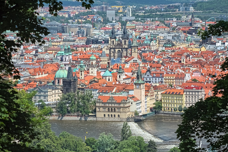 View of the Old Town of Prague from Petrin Hill, Czech Republic. Photo taken by telephoto lens through the gap between trees.