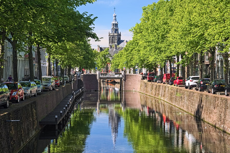 GOUDA, NETHERLANDS - MAY 24, 2015: View on the tower of Sint Janskerk (St John the Baptist Church) and Nood-Godsbrug bridge from Uiterste bridge across the Gouwe river in sunny day.