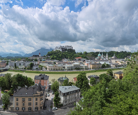 Salzburg, Austria. View over the Salzach river, Old Town and Hohensalzburg fortress with low cumulus clouds above them. View from the fortified wall at the Kapuzinerberg mountain.