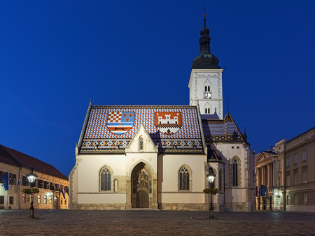 St. Marks Church in Zagreb at dusk, Croatia. Tiles on the churchs roof are laid so that they represent the coat of arms of Zagreb (right) and Triune Kingdom of Croatia, Slavonia and Dalmatia (left).