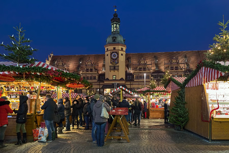 LEIPZIG, GERMANY - DECEMBER 16, 2018: Christmas market at Marktplatz (Market square) in front of the Old Town Hall at dusk. The Leipzig Christmas Market tradition dates back to 1458.