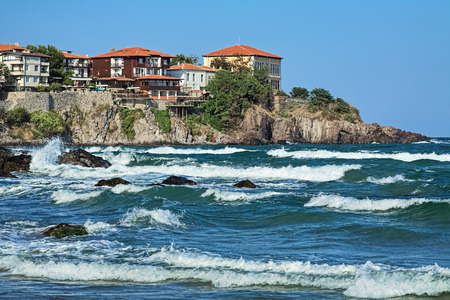 Sozopol, Bulgaria. East cape of Sozopol Old Town (former ancient town of Apollonia) with yellow building of Art Gallery. View from the citys central beach across the bay with storm waves.