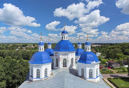 Kashin, Russia. View from the Bell Tower of the Resurrection Cathedral over the cathedral's cupolas and eastern part of the town in sunny summer day with cumulus clouds on the sky.