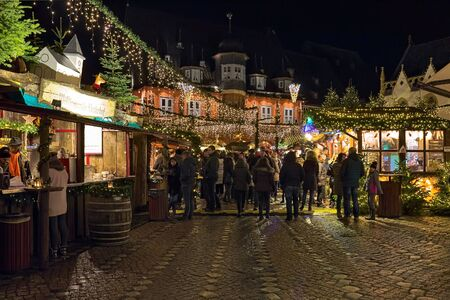 Goslar, Germany. Christmas market at Market Square around the Market Fountain in night. Red guildhall Kaiserworth and fragment of gothic Town Hall are visible in the background. 免版税图像