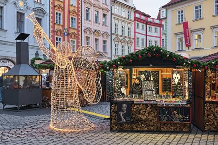 Prague, Czech Republic. Small Christmas market with figure of angel with horn made of the lights garlands at the Male Namesti (Small Square) not far from the Old Town Square.