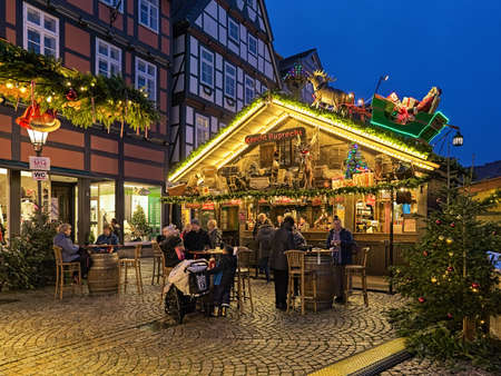 CELLE, GERMANY - DECEMBER 6, 2018: Xmas chalet decorated with old things, Christmas reindeer and Santa Claus on his sleigh at Christmas market on Grosser Plan square in Old Town in dusk.