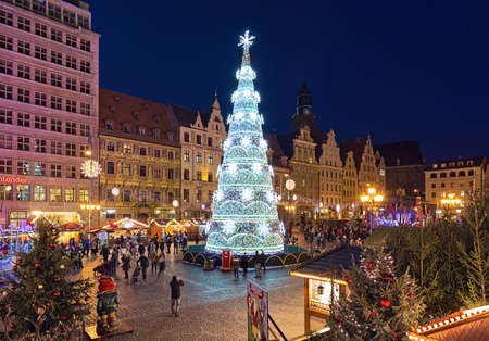 WROCLAW, POLAND - DECEMBER 9, 2019: The city's main Christmas tree at Christmas market on the Market Square in dusk. Wroclaw Christmas Market is regarded as one of the best Christmas markets in Poland 新聞圖片