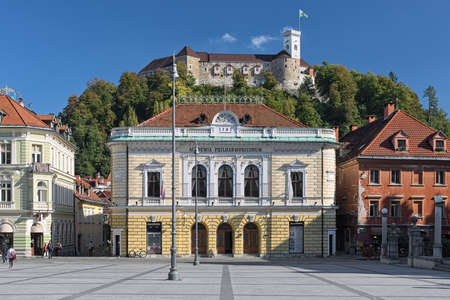 LJUBLJANA, SLOVENIA - OCTOBER 4, 2018: Slovenian Philharmonic Building and Ljubljana Castle. The building was constructed in 1891 by design of Adolf Wagner. The castle was founded in the 11th century.