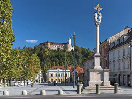 LJUBLJANA, SLOVENIA - OCTOBER 4, 2018: Congress Square with Holy Trinity Column on the foreground and Slovenian Philharmonic Building at the opposite side on the background of Ljubljana Castle.