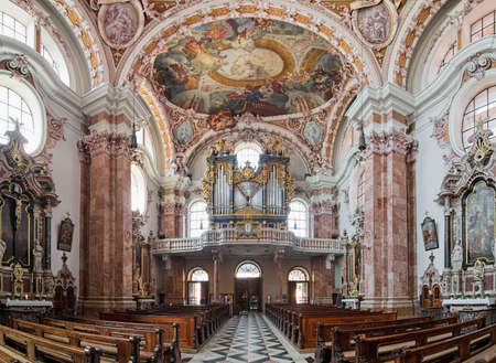 INNSBRUCK, AUSTRIA - MAY 26, 2017: Panoramic view of interior of Innsbruck Cathedral with main organ. The cathedral was built in 1717-1724. The organ was built in 1725 and reconstructed in 1998-2000. Editorial