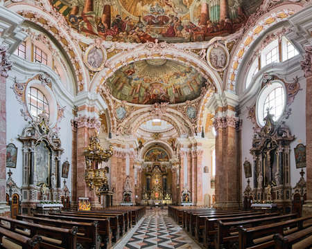 INNSBRUCK, AUSTRIA - MAY 26, 2017: Panorama of interior of Innsbruck Cathedral. The cathedral was built in 1717-1724. The interior, including ceiling fresco, was created by Asam brothers in 1722-1724. Editorial