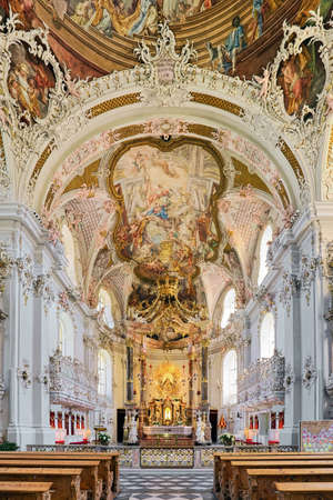 INNSBRUCK, AUSTRIA - MAY 27, 2017: Chancel, choir and high altar of Wilten Basilica. The rococo interior was created in 1751-1756. Statue of Our Lady with child on high altar is from the 14th century.