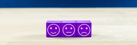 Customer service satisfaction concept - three wooden dices with different expressions of satisfaction on them.