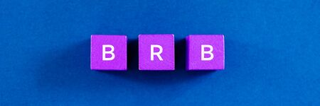 Top view image of BRB abbreviation spelled on violet colored wooden dices. Over blue background.