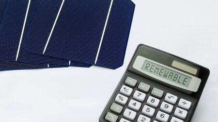 Solar energy cells with calculator showing the word Renewable in a conceptual image for sustainable energy sources 版權商用圖片