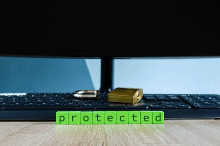 Broken padlock on computer keyboard in conceptual image with green blocks spelling the word protected