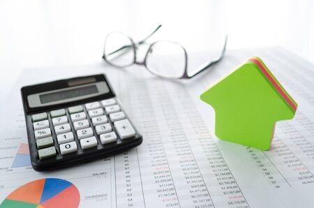 Business concept for buying or saving for a house with , calculator, eyeglasses, house shape and documents