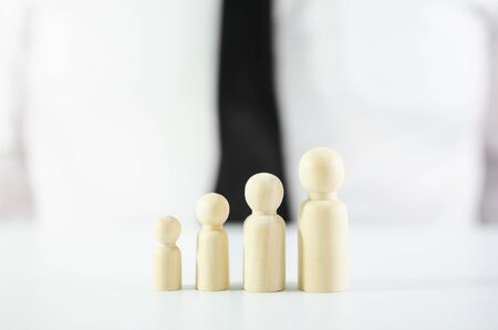 Four wooden figures placed in a row increasing in size in front of a businessman in conceptual image for personal development or becoming a leader