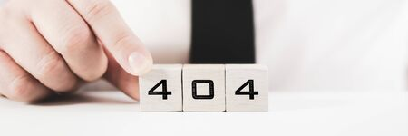 Businessperson assembling a sign 404 on white blocks in conceptual image for page not find error message Фото со стока
