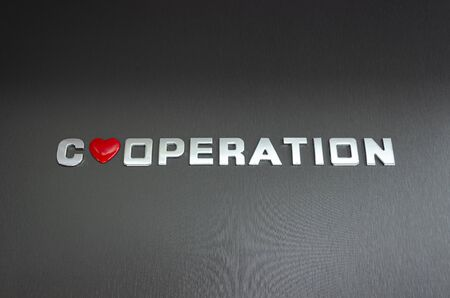 Cooperation concept. Word cooperation spelled with chrome letters, with a red heart symbol replacing the letter o.
