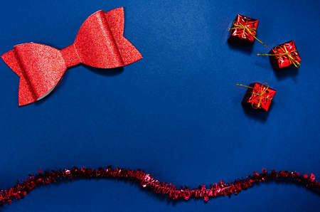 Top view of red christmas decorations in a conceptual image of the coming new year. Over blue background.