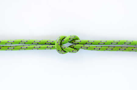 Reef knot on tied on a green rope on isolated white background Banco de Imagens