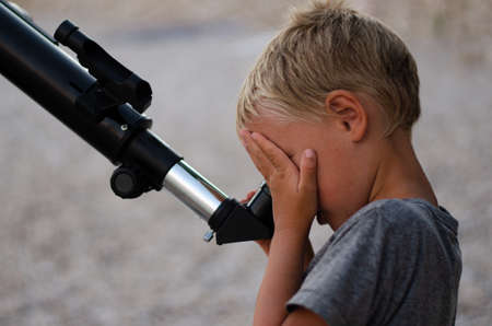 Young boy on a pebble beach looking through a telescope at the evening sky, covering one eye with his hand.