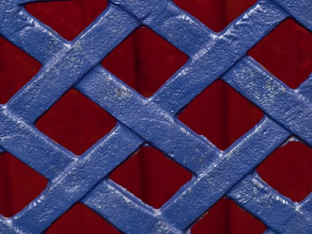 Plait in blue cast iron on red background non figurative for background.  Stock Photo