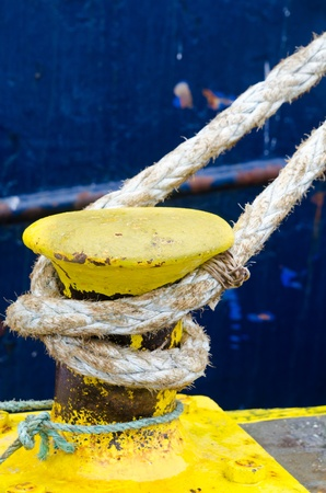 the mooring: Mooring line tied to yellow rysty bollard on blurred blue vessel.