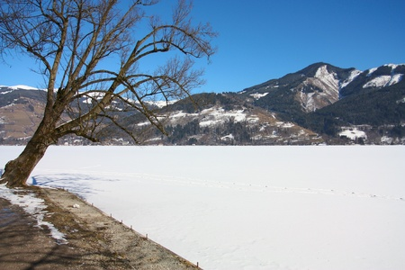 Scenic view of path around lake with snow capped mountains in background, Zeller See, Zell am Zee, Austria
