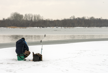 Fisherman sitting on an ice floe and fishing in the hole.