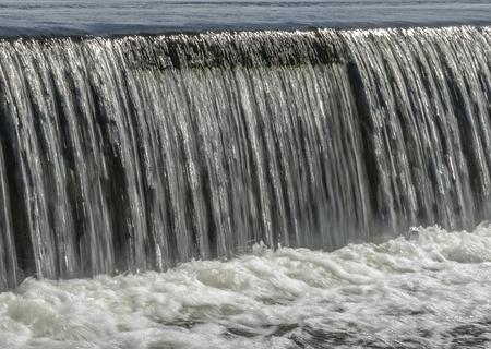 El agua fluye por el aliviadero de una pequeña presa de hormigón.