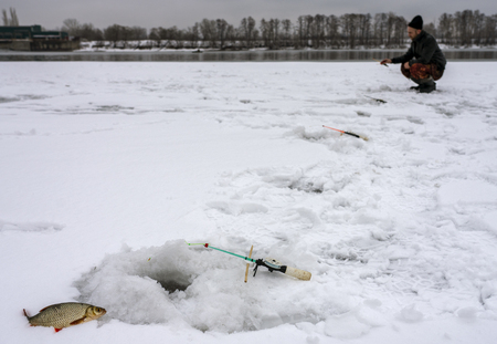 Winter fishing, caught roach lying next to the hole in the background fisherman bent over the hole. Banque d'images