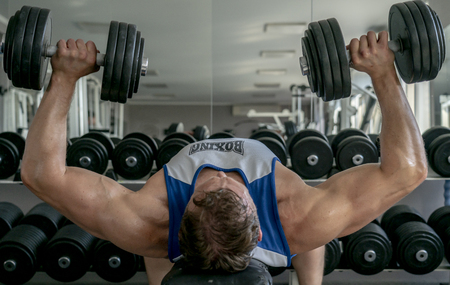 Athlete bodybuilder pumping muscles in the gym, performs a bench press the dumbbells Stockfoto