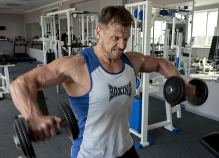 Athlete bodybuilder shakes muscles in the gym, performs wiring dumbbells Stock Photo