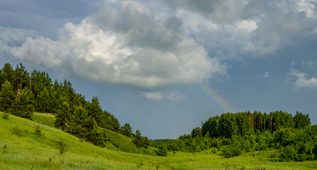 Rainbow over the forest coming down from a big cloud Zdjęcie Seryjne
