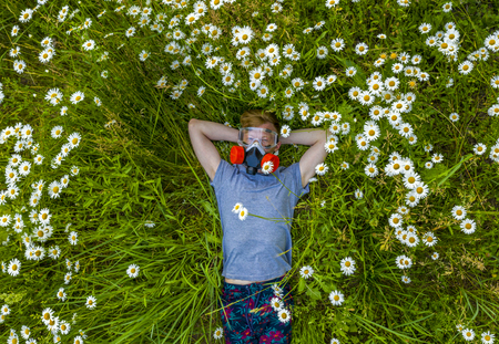 a person with an Allergy in a respirator and goggles is lying on a field of daisies and enjoys the aroma of fresh air