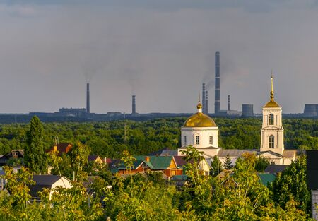 the Church is lit by the sun against the grey of the pipes metallurgical plant Фото со стока