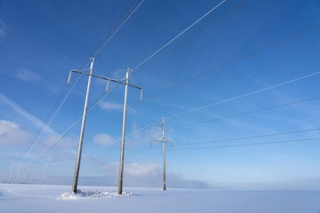 Electric power transmission in the field in the winter against the blue sky