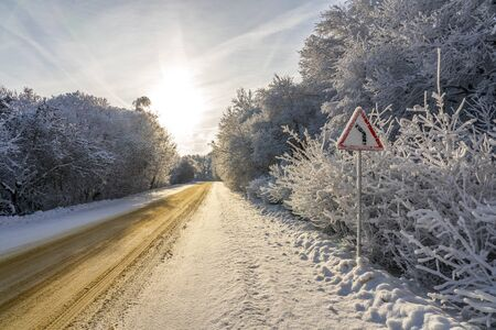 Traffic sign turn right on snowy road. Horizontal image. Background with cloudy sky and dry branches of trees with snow. Stockfoto