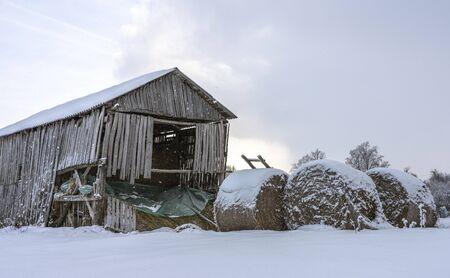 Round bale of straw under the snow