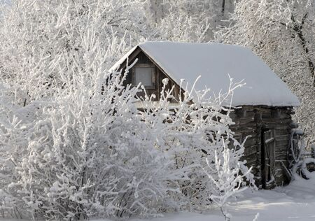 Old wooden shed during heavy snowfall