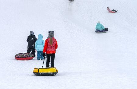Children in colorful garments slide down the slide on inflatable rings Zdjęcie Seryjne